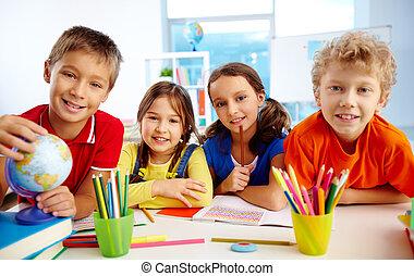 Group of diligent schoolchildren looking at camera in school