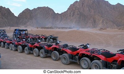 Group of Red Quad Bikes stand in a parking lot in desert on...