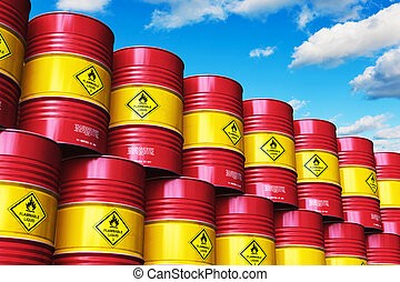 Group of red stacked oil drums against blue sky with clouds