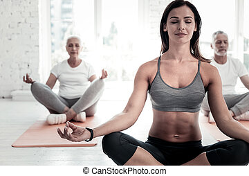 Group of retired people meditating during yoga class