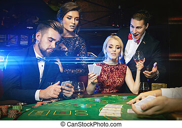 Group of rich people is playing poker in the casino