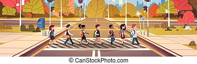Group Of School Children Crossing Road On Crosswalk With...