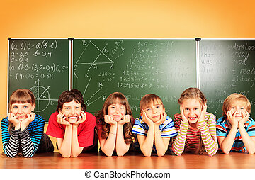 studying in classroom - Group of school children studying in...