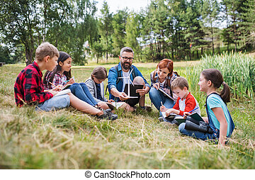 Group of school children with teacher and windmill model on field trip in nature.