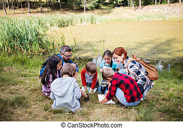 Group of school children with teacher on field trip in nature.