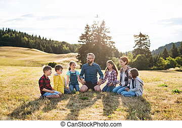 Group of school children with teacher on field trip in nature, holding hands.
