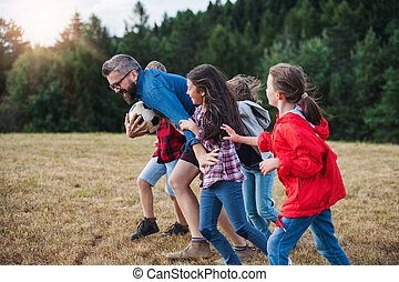 Group of school children with teacher on field trip in nature, running.