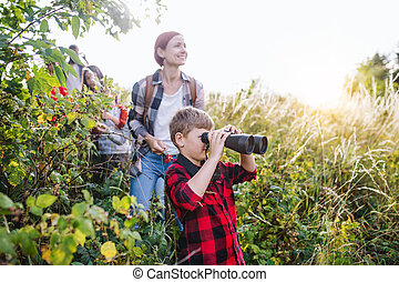Group of school children with teacher on field trip in nature, using binoculars.