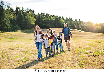 Group of school children with teacher on field trip in nature, walking.