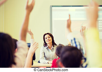 group of school kids raising hands in classroom - education...