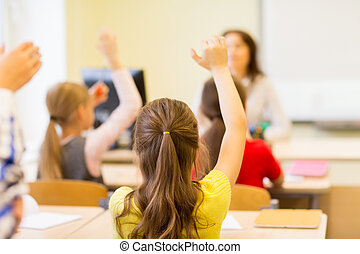 group of school kids raising hands in classroom - education,...