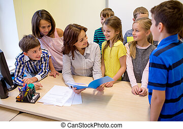group of school kids with teacher in classroom - education,...