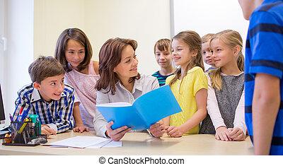 group of school kids with teacher in classroom