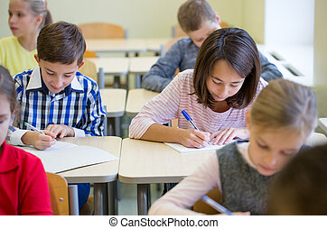 group of school kids writing test in classroom