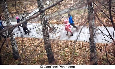 group of schoolchildren go to the park in autumn