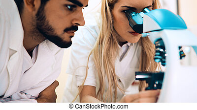 Group of scientists doing research looking through microscope