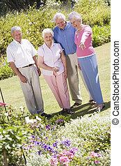 Group of senior friends in garden Group of senior friends in...