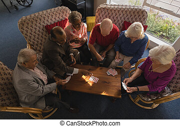 Group of senior friends playing cards at nursing home