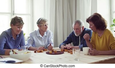 Group of senior people in community center club, playing...