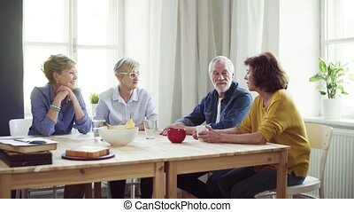 Group of senior people sitting at the table in community...