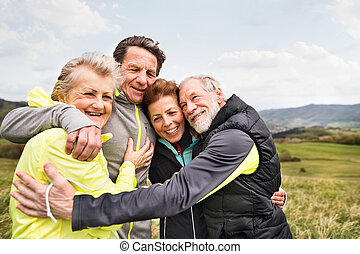 Group of senior runners outdoors, resting and hugging. -...