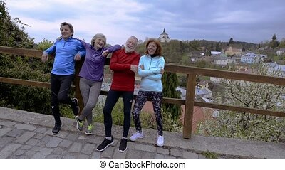 Group of senior runners posing outdoors in the old town. -...