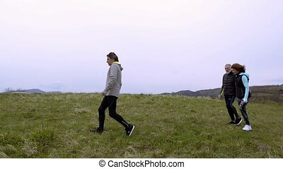 Group of senior runners walking outside on the green hills....
