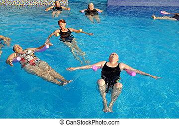 Group of senior women doing exercise in pool.