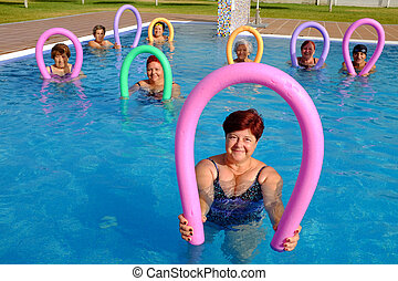 Group of seniors about to do exercise in pool.