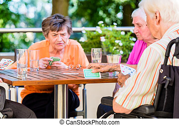 Group of seniors playing board game on terrace of retirement home