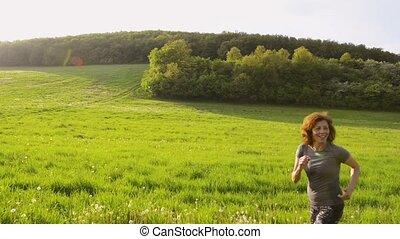 Group of seniors running outside on the green hills. - Group...