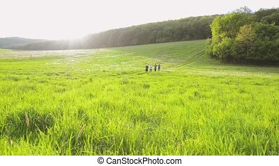 Group of seniors running outside on the green hills. - Group...
