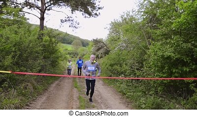 Group of seniors running race in nature on dirt road. - ...