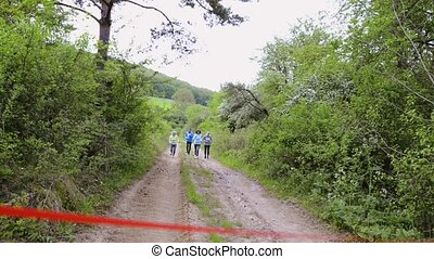 Group of seniors running race in nature on dirt road. -...