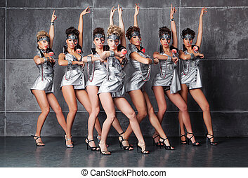Group of seven happy cute girls in silver go-go costume ready to party