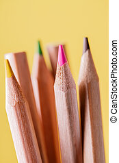 group of sharpened colorful pencils on yellow background.