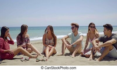 Group of six friends sitting in sand on beach - Group of six...