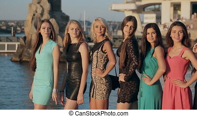 Group of slender models wearing dresses waving hands close to the sea
