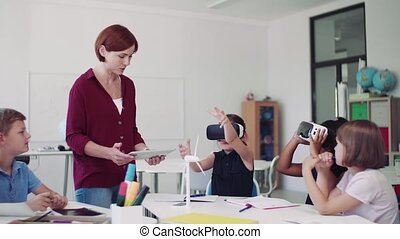 Group of small school kids with VR goggles and teacher in ...