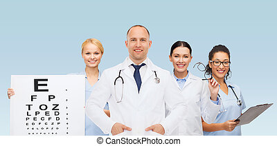 medicine, profession, teamwork and healthcare concept - international group of smiling medics or doctors with eye chart, clipboard and stethoscopes over blue background