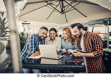 Group of smiling friends in cafe looking at laptop - We are ...
