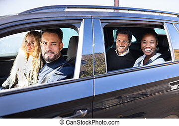 Smiling Friends In Car On Road Trip Together