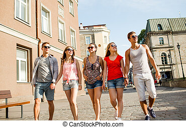 group of smiling friends walking in city