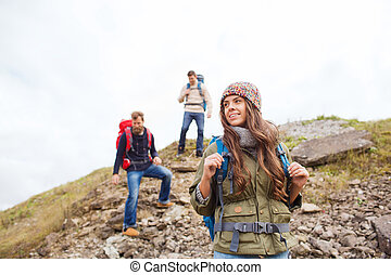 adventure, travel, tourism, hike and people concept - group of smiling friends with backpacks walking down downhill