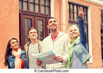 group of smiling friends with map exploring city - travel,...