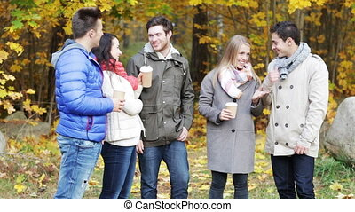 group of smiling men and women in autumn park