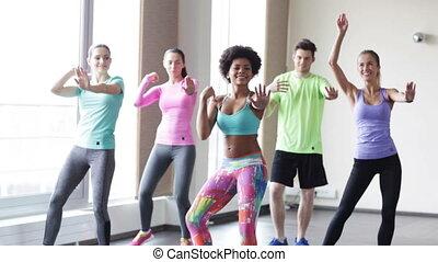 group of smiling people dancing in gym or studio
