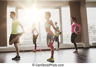 group of smiling people exercising in gym