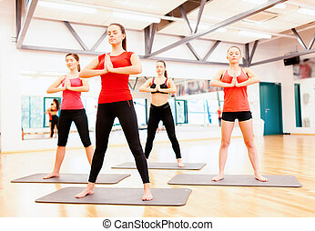 group of smiling people meditating in the gym - fitness,...