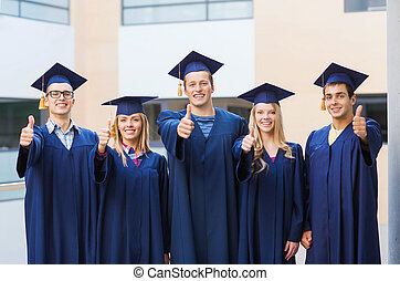 group of smiling students in mortarboards - education,...